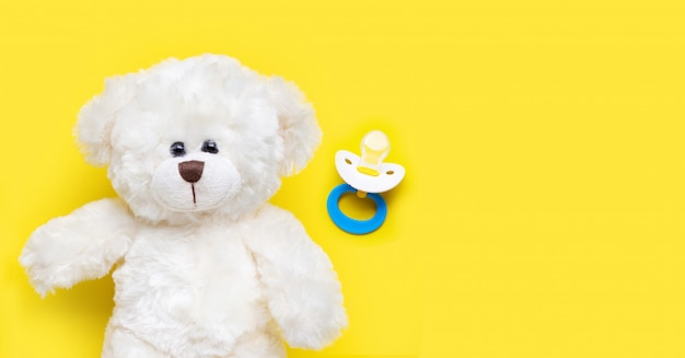 Baby pacifier with toy white bear on yellow.