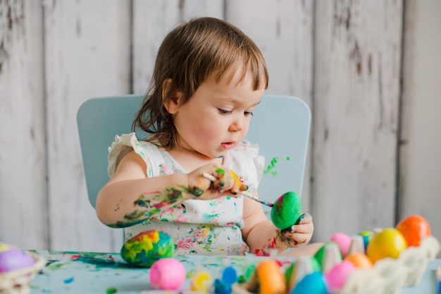 Baby painting easter eggs