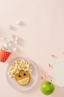 아침에 아기 팬케이크. 아이 디저트를위한 창의적인 아이디어 : 팝콘을 만드는 머리카락으로 행복한 얼굴 형태의 맛있는 팬케이크