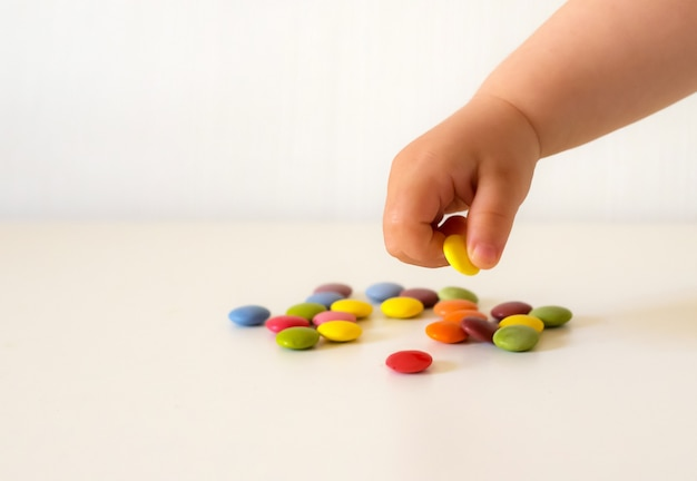 Baby picking up colorful candies on white background