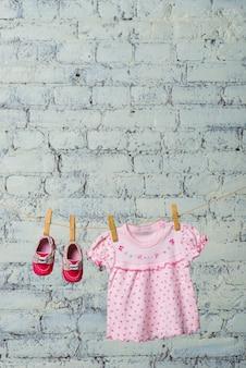 베이비 핑크 드레스와 소녀를위한 빨간 신발, 흰색 벽돌 벽에 밧줄에 건조.