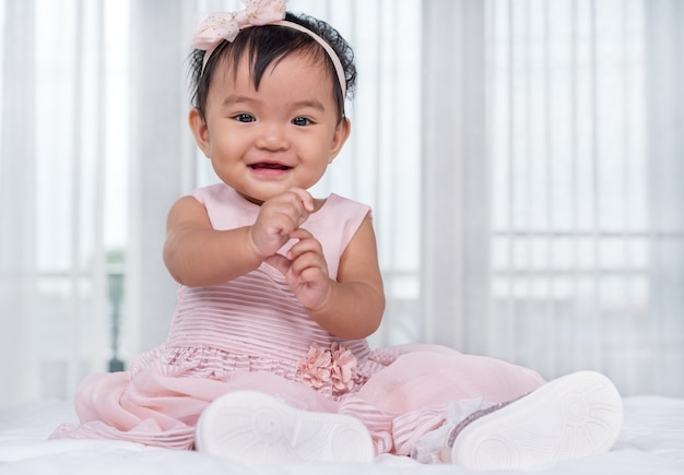 Baby in pink dress on bed