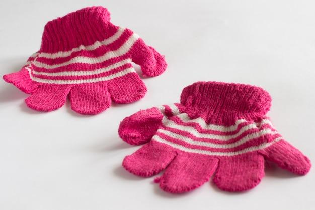 Детские розовые перчатки на белом фоне