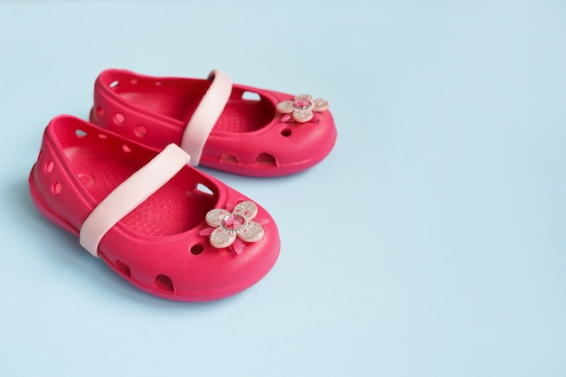 Baby pink rubber summer shoes on blue wall with copy space