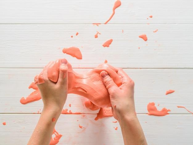 ベビーピンクのスライムは白いテーブルに塗抹標本します。おもちゃの抗ストレス。手の運動能力の発達のためのおもちゃ。
