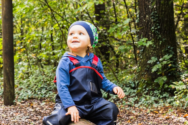 Baby playing on a forest path in autumn