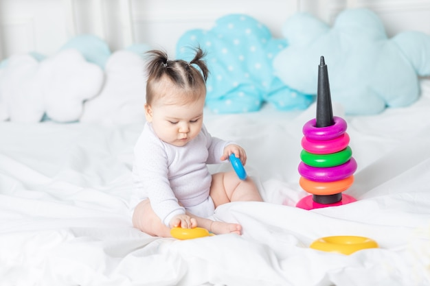 집 피라미드의 침대에서 노는 아기, 행복한 사랑하는 가족의 개념과 아이들의 발달