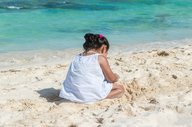 Baby playing in the sand near the sea. little girl sitting on the beach. silhouette of little girl with the sea in the background. building sand castle
