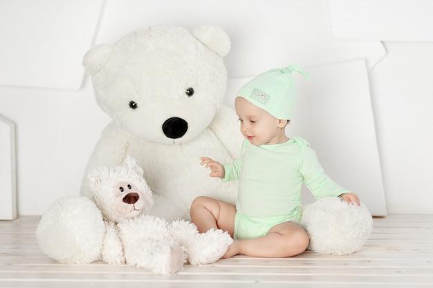 Ребенок играет с большим плюшевым мишкой дома в светлой комнате, детская игра и концепция досуга