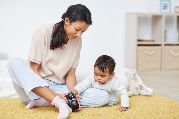 Младенец играя с часами дома