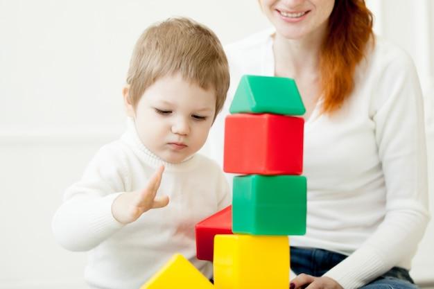 Ребенок играет с красочными игрушечными блоками