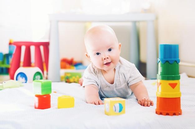家で色とりどりのおもちゃで遊ぶ赤ちゃん幸せな生後6ヶ月の赤ちゃんの遊びと発見