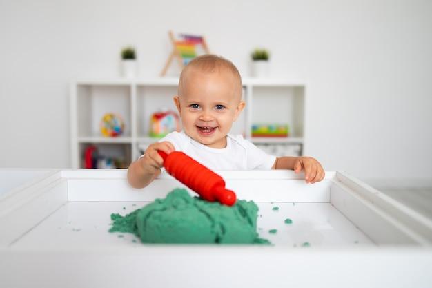 Ребенок играет с зеленым кинетическим песком и скалкой