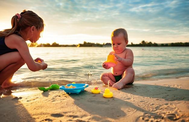 해변에서 누나와 노는 아기. 프리미엄 사진