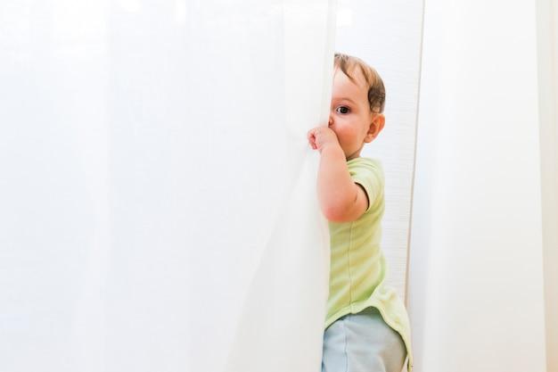 白いカーテンで遊ぶ赤ちゃん