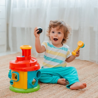 Baby plays on the floor in the room in educational plastic toys.