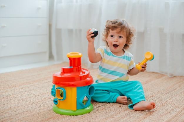 Малыш играет на полу в комнате в развивающие пластиковые игрушки.