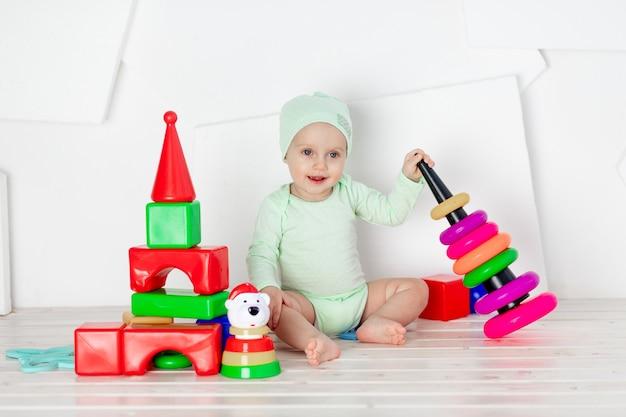 Малыш играет с игрушками в детской комнате дома в зеленом боди, концепция развития и досуга малышей