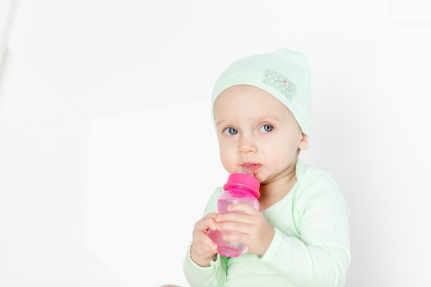 赤ちゃんは、幼児の発達と余暇の概念である緑のボディスーツを着て、自宅の子供部屋でおもちゃで遊ぶ