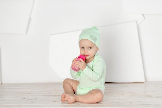 아기는 녹색 바디 수트, 유아의 발달 및 여가 개념으로 집에있는 어린이 방에서 장난감을 가지고 노는