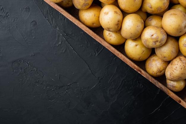 ベビーポテトインドからの小さな丸いポテトセット、木製の箱、黒い石の背景、上面図フラットレイ、コピースペースとテキスト用のスペース