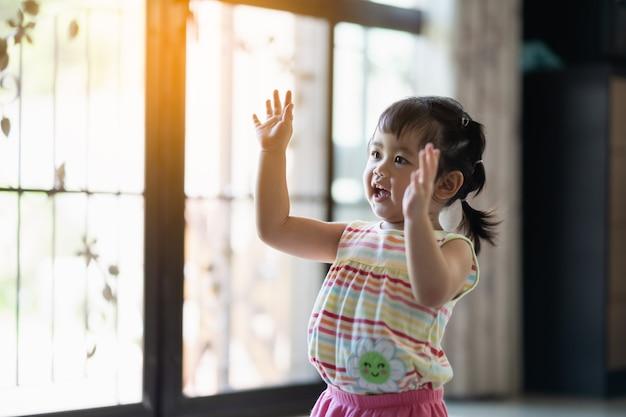 Ребенок поднимает руку и улыбается в доме