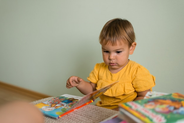 Baby reading colorful books in ukrainian at home