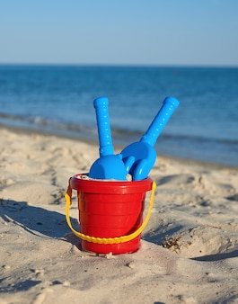 Baby red plastic bucket with sand and shovel on the seashore