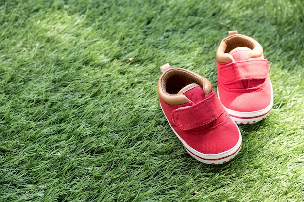 Baby red shoe on artificial grass