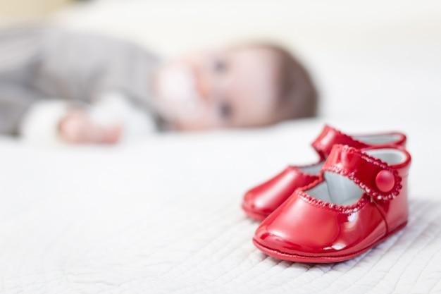 Детские красные туфли и младенец, лежащий на заднем плане