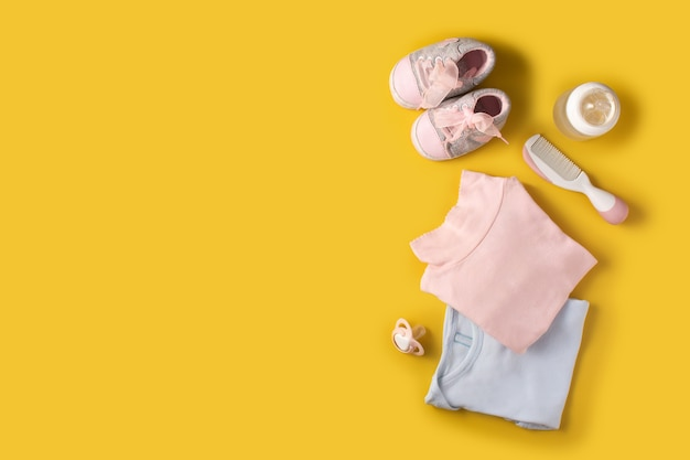 Baby rompers, shoes, feeding bottle, pacifier and hair comb on yellow background