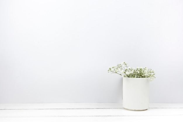 Baby's breath flowers in ceramic vase on white wooden table
