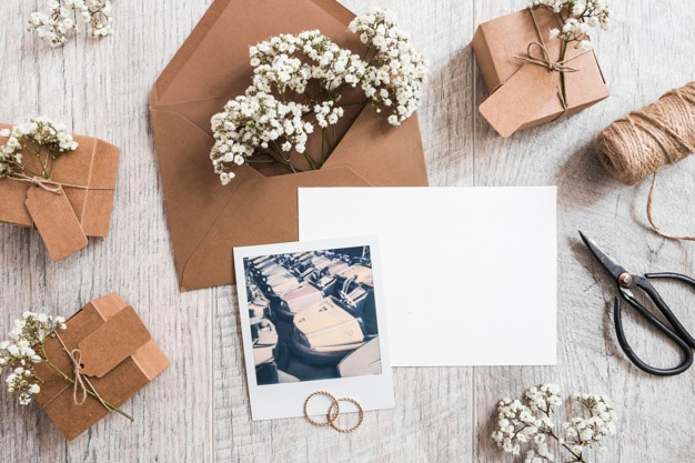 Baby's-breath flowers in the envelope with blank paper; wedding rings; spool and polaroid frame