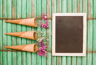Baby's-breath flowers in cone with wooden blank slate on green wooden shutter backdrop