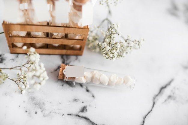 Baby's-breath flowers and marshmallow test tubes on textured background