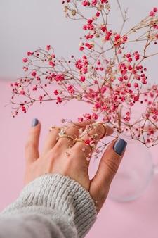 아기의 숨결. 암시. 보석 반지와 여자의 손입니다. 보석과 럭셔리 컨셉입니다. 세련 된 액세서리와 함께 아름 다운 여자입니다. 식물 미학. 핑크 파스텔 색상