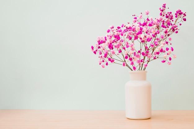 色のある背景の木製の机の上に白い瓶のピンクのbaby's-breathの花
