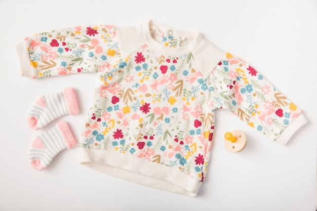 Детская одежда и носки с соской, изолированные на белом фоне