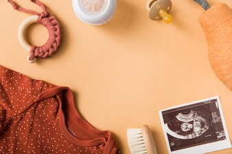 Baby's clothing; brush; toy; pacifier; stuffed pear and sonography picture on an orange background