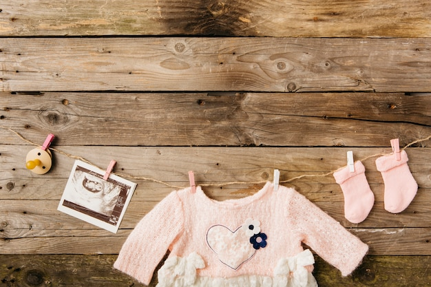 Baby's dress; socks; pacifier and sonography picture hanging on clothesline with clothespins against wooden wall