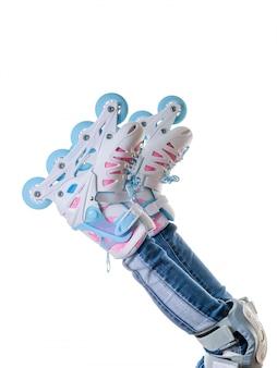 白い背景に分離されたマルチカラーのローラースケートで赤ちゃんの足。