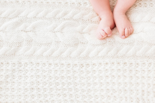 Baby's feet on white knitted background.