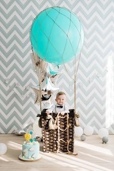 赤ちゃんの最初の誕生日。かわいい微笑の赤ん坊は1歳です。風船で子供たちのパーティーの概念