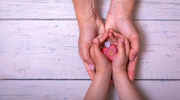 어머니의 손에 하트를주는 아기의 손. 아이와 엄마 사이의 사랑과 관심. 어머니의 날 또는 여성의 날 개념.