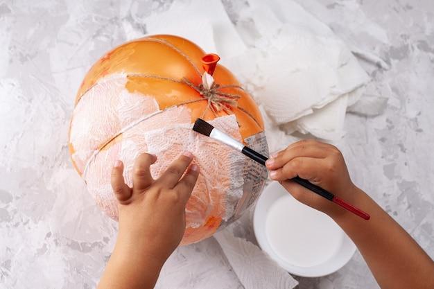 Руки малыша лепят тыкву из папье-маше из воздушного шара, на хеллоуин своими руками изолированно