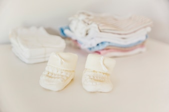 Baby's knitted sock in front of diaper and clothing stacked