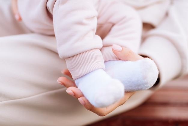 赤ちゃんの足と母親の手をクローズアップ