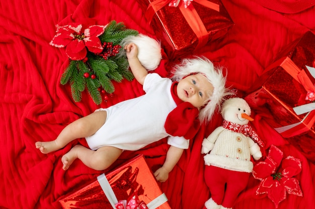 Baby in a santa costume sleeping on a light wooden background