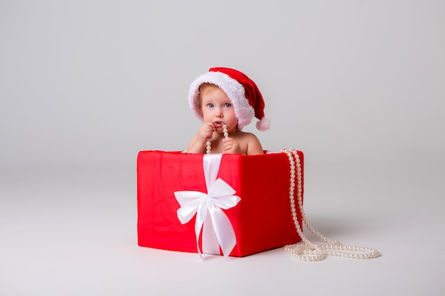 Baby santa sits in a red gift box on light isolate, space for text