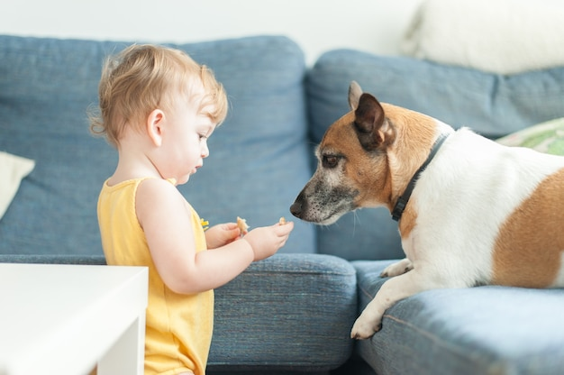 Baby sharing cookie with dog